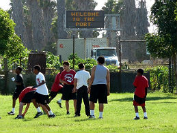 Teenagers play soccer beneath a sign that reads