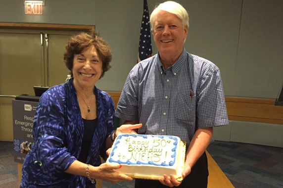"Linda Birnbaum and Chip Hughes holding a cake with ""Happy 50th Birthday NIEHS"" written in icing"