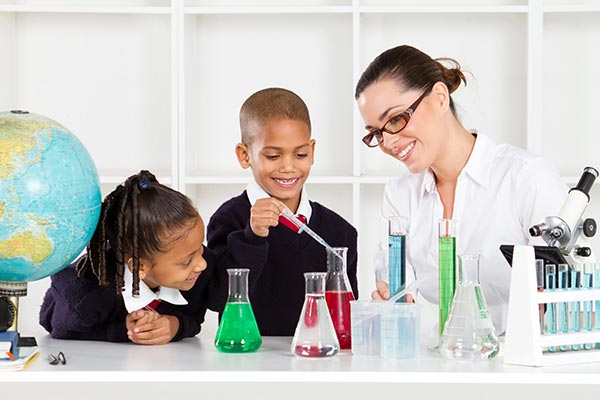 Teacher helping a girl in chemistry lab