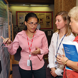 Three female colleagues conversating in front of the information board