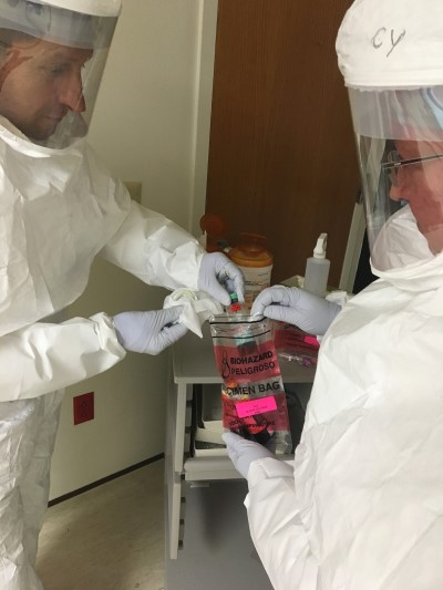 Two workers in HAZMAT suits putting a biohazard in a specimen bag