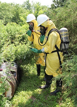 WTP Trainees assessing disposed waste with monitoring devices and safety gear
