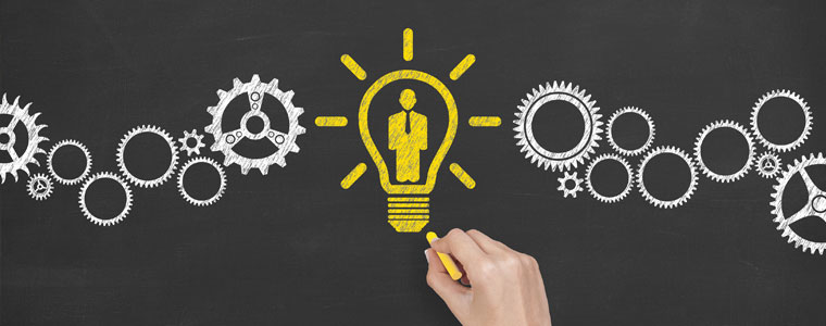 Chalk drawing of gears and a man inside a lightbulb