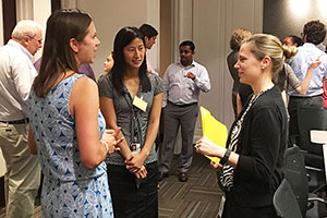 Kirsten Verhein, Ph.D., left, and Gabor, center, talked with an INC Research participant during the informal networking portion of the July 7 site visit