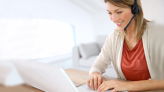 woman with headset sitting at laptop