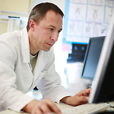 man wearing a white lab coat sitting in front of a computer