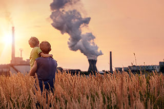 father holding son while looking at smoke stack