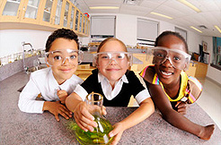 Children in a science lab wearing protective eye gear.