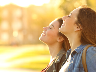 2 women in profile with eyes closed and smiling outside on a sunny day
