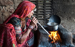 woman sitting by outdoor cook stove