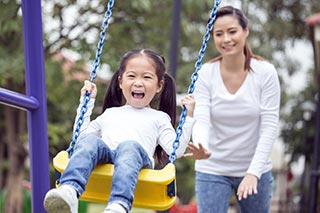 mom pushing girl on swing