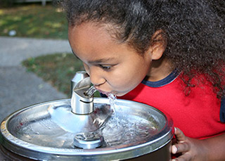 Little girl drinking from a water fountain