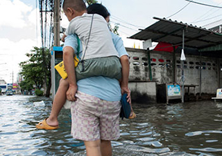 man carrying child in flooded area