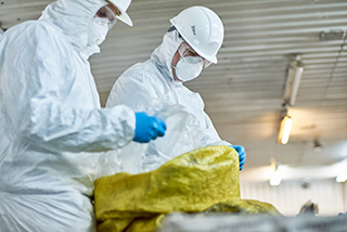 workers wearing biohazard suits working at waste processing plant sorting recyclable plastic on conveyor belt