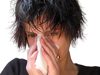 Woman with tissue covering her nose as if sneezing