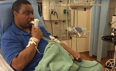 man using an inhaler in a hospital bed