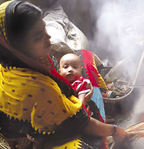 woman holding infant and cooking over fire