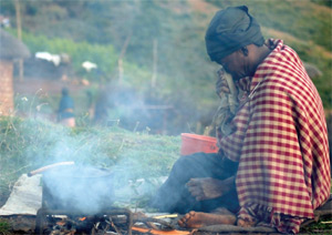 A woman sitting my a fire cooking, in the developing country side