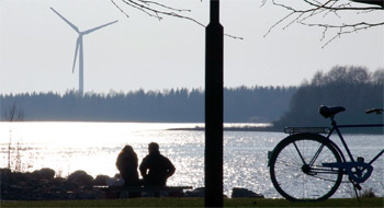 photo of a couple sitting by a river. In the background is a wind turbine.