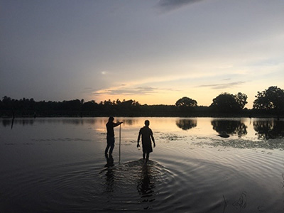 two people on the water at dusk
