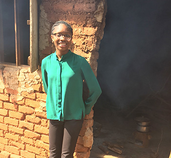 Adaeze Wosu, in front of a rural household kitchen in Eastern Uganda