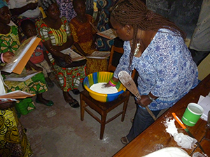 A study team member (pictured in front) trains women on the cassava wetting method