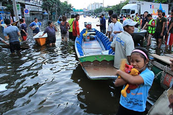 Evacuees in Thailand walk through a flooded street after severe flooding, little girl holds stuffed animals