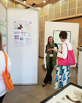 picture from the event where a student is presenting her research on a poster
