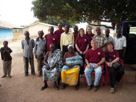 Phillips and his group poses for a photo outside with the villagers in Ghana