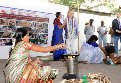 Dr. Kalpana Balakrishnan talks with U.S. Secretary of State Hilary Clinton about the clean cookstoves effort in South India, as two women demonstrate cooking on different cookstove models.
