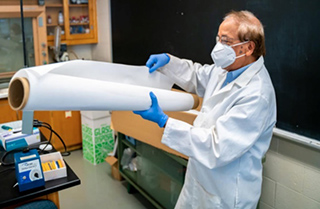 Dibakar Bhattacharyya, Ph.D., in the lab with a large sheet of membrane.