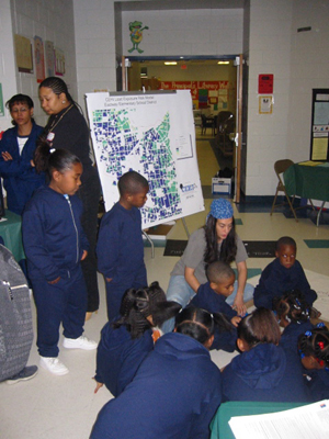 An outreach staff member shows a large group of children a map