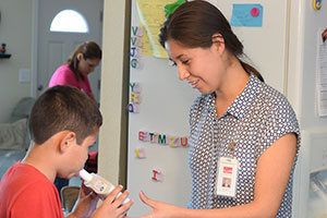 staff member coaches a patient during an asthma test