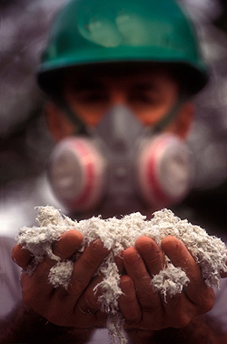 Worker holding handfuls of asbestos product while wearing respirator