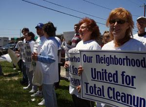 "Protesters holding signs that read ""Our Neighborhood United for Total Cleanup"""