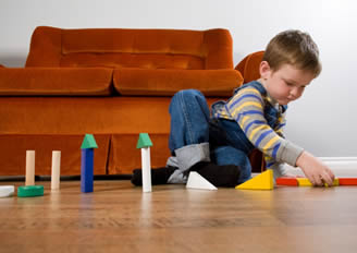 child playing on floor with sofa in background