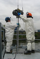 Two people in protective gear adjust a cable