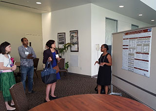 James-Todd presents her poster to an engaged audience at the Environmental Health Sciences Core Centers' meeting, held July 2018 in Davis, California