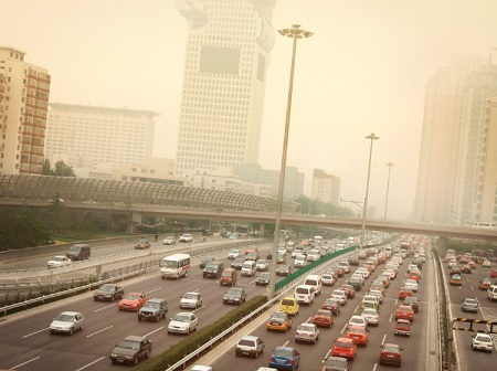 A highway with heavy traffic and heavily polluted skyline in the distance