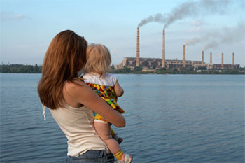 woman and child looking at smoke stacks from a distance