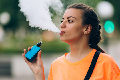 Picture of young woman vaping and blowing out smoke