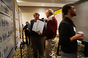 In addition to providing welcome remarks, Woychik, center, judged student posters.
