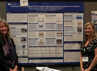 Michelle Heacock, Ph.D., and Heather Henry, Ph.D., standing in front of their poster