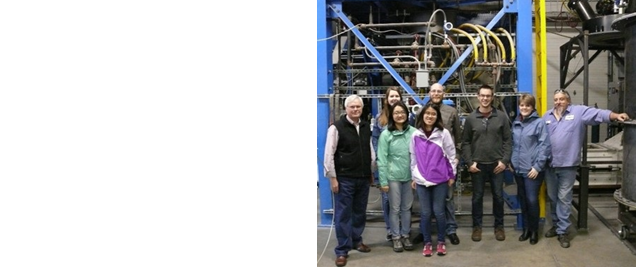 A group of people standing in front of industrial equipment