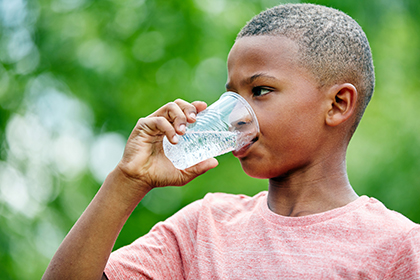 boy drinking a cup of water