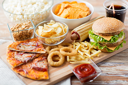 various food items like pizza, onion rings, french fries, burger, ketchup, soda