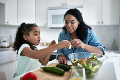 parent and child preparing vegetables at home