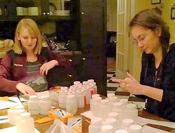 Two female scientists assemble water sampling kits of plastic bottles