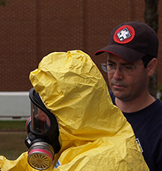 Roy Stover assists a trainee during a hazardous materials hands-on training.