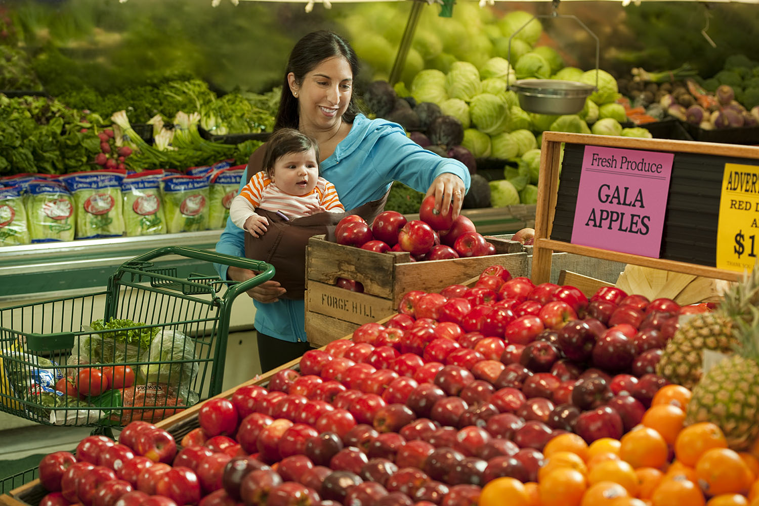 Woman with baby picking out fresh fruit at market